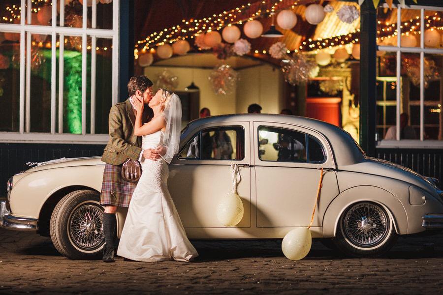errol park wedding - couple kiss by wedding car