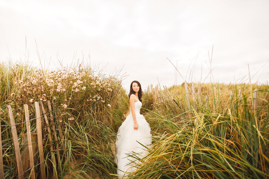 Scottish elopement photography in St Andrews, Fife - bride poses in long grass at beach
