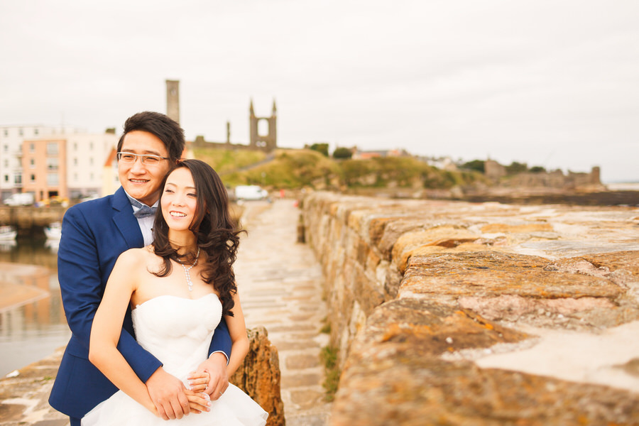 Scottish elopement photography in St Andrews, Fife - bride and groom embrace on pier