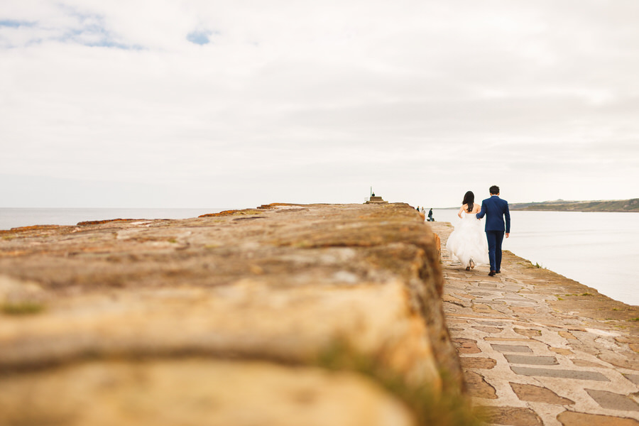Scottish elopement photography in St Andrews, Fife - bride and groom walking on pier